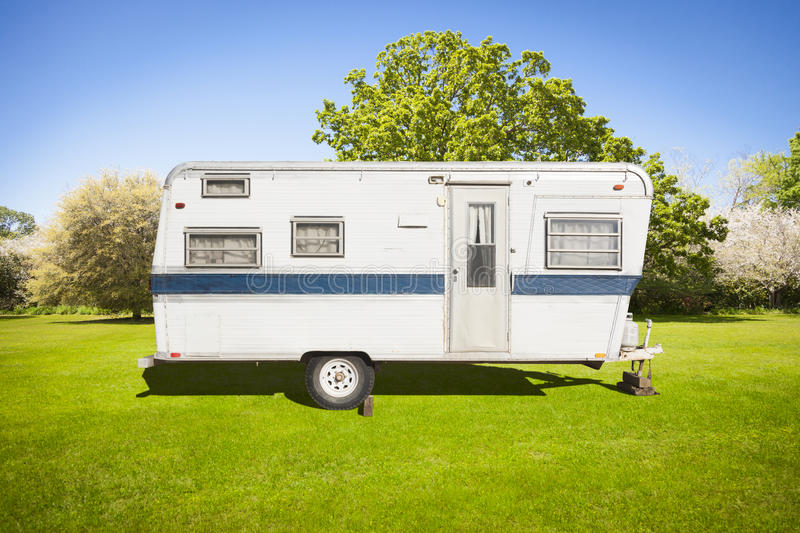 Cute Classic Old Camper Trailer In Grass Field. Classic Old Camper Trailer In Grass Field with Beautiful Trees royalty free stock image