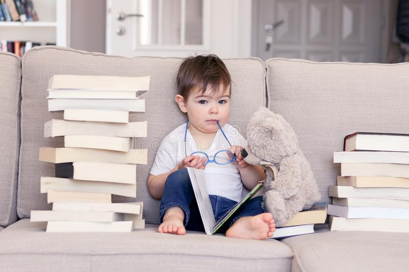 Cute clever funny little baby boy with thoughtful serious face expression holding glasses in hands reading book sitting on sofa wi stock photography