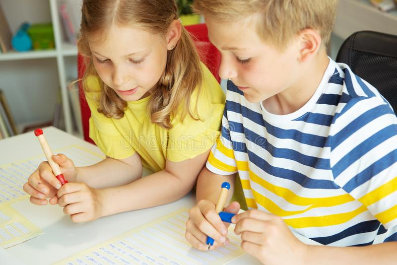 Cute clever schoolchildren are came back to school and studying together at the table royalty free stock images