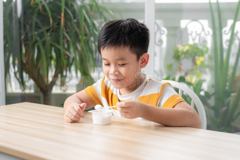 Cute Colboy som äter yoghurt för frukost fotografering för bildbyråer