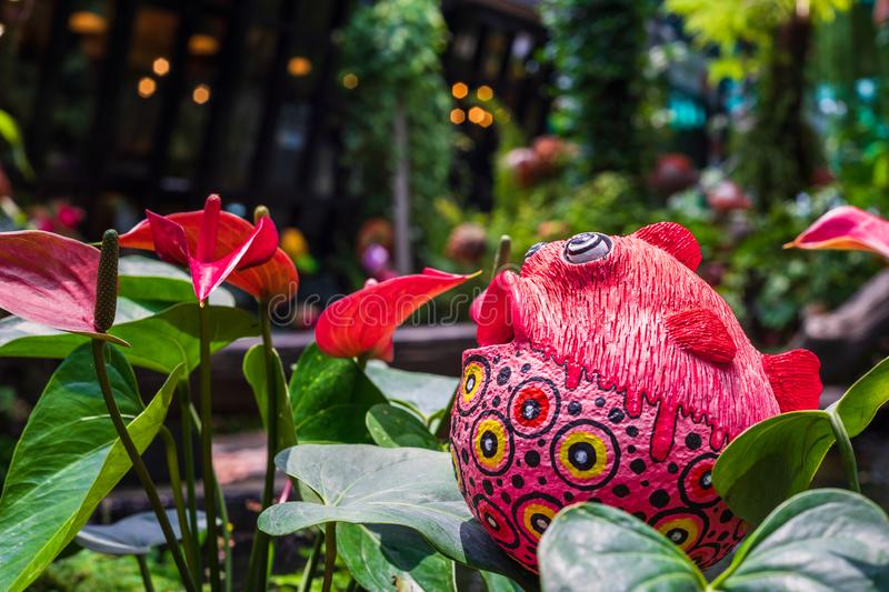 Cute colorful fish statue and Red anthurium flowes ( tailflower, flamingo flower, laceleaf ) decoration in the garden stock image