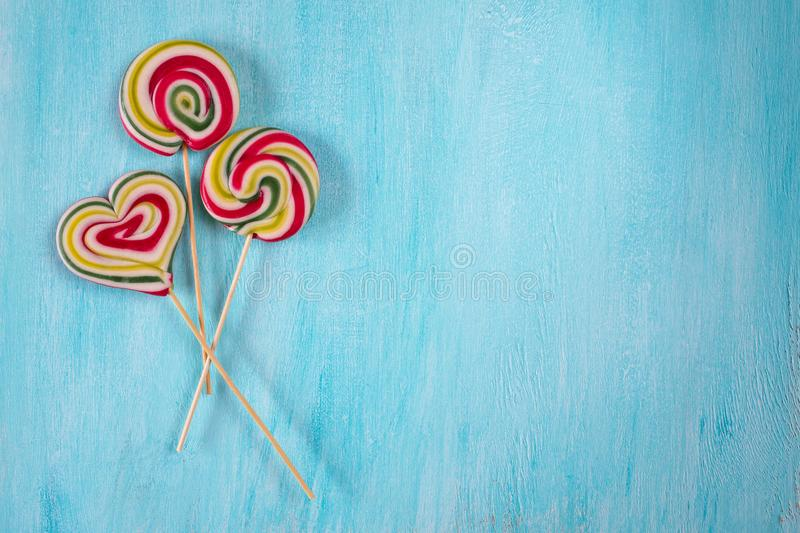Cute colorful round lolipop and lollipop looks like a heart on turquoise background royalty free stock images