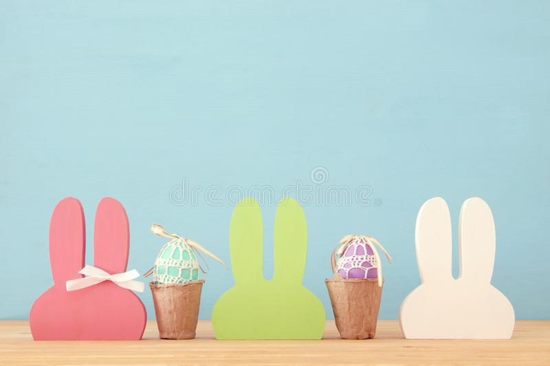 Cute colorful wooden bunny ears and easter eggs over wooden table. royalty free stock image