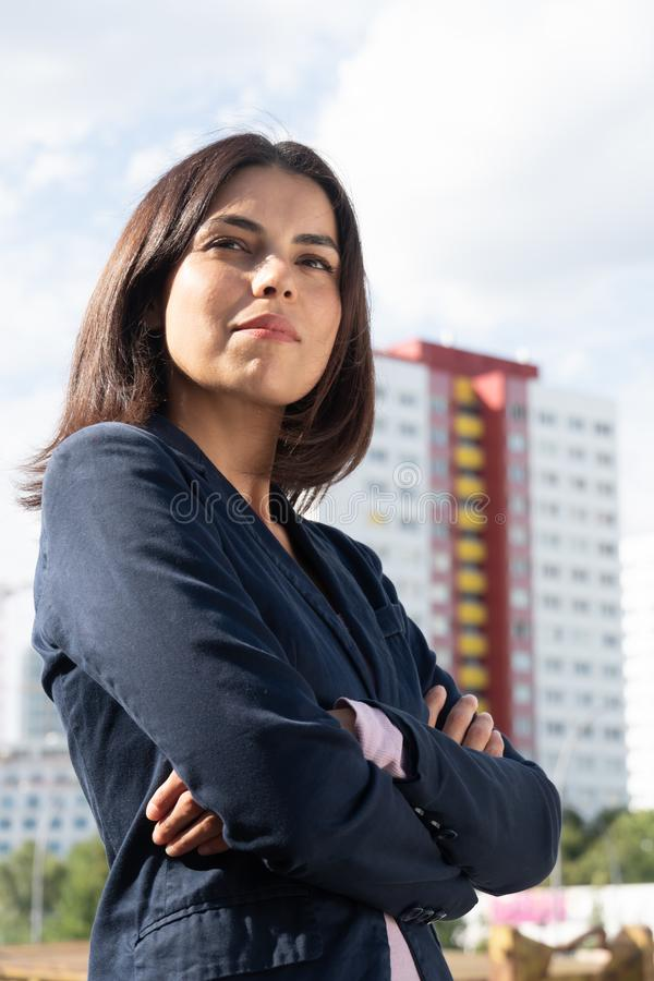Cute and confident businesswoman posing. Portrait of a young businesswoman standing against high buildings and crossing her arms stock photo