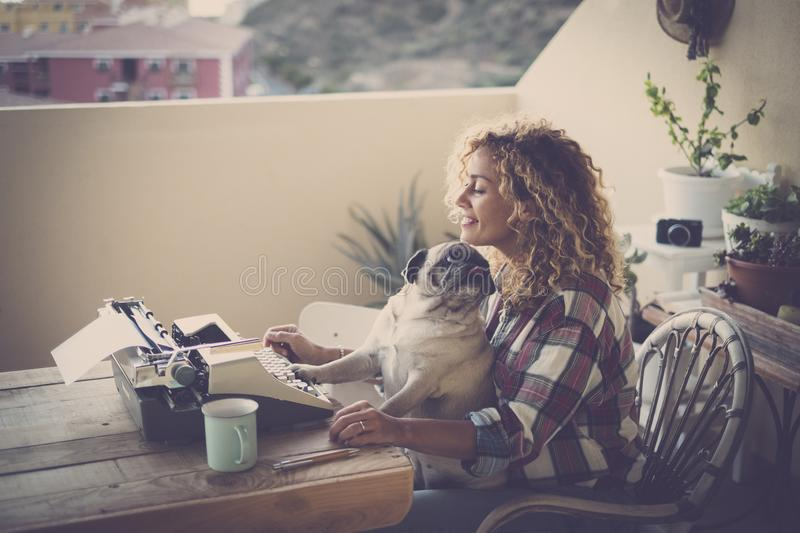 Cute couple of best friends together - woman with pug sitting on her legs, old job writing with a type machine in the terrace of. Her house - outdoor girl with royalty free stock photo