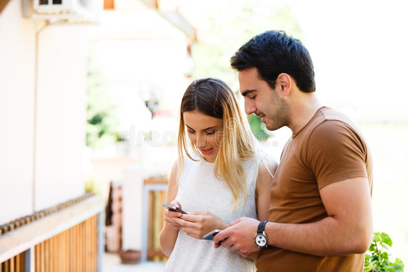 Cute young couple standing and using phone stock images