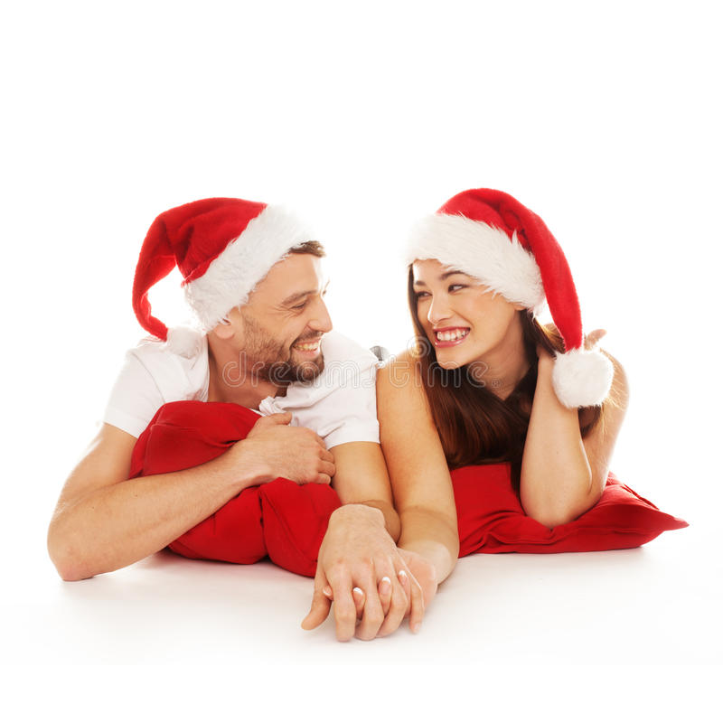 Cute couple in christmas hats. Cute couple smiling holding hands and wearing christmas hats royalty free stock photography