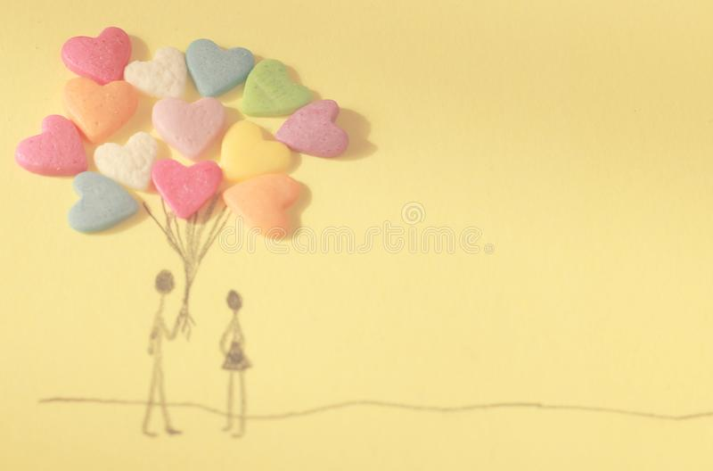 Cute couple drawing with candy hearts as balloons stock images