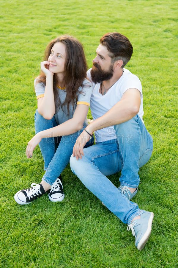 Cute couple. fashion couple having fun together. cute girl and bearded man hipster on green grass. couple in love stock photography