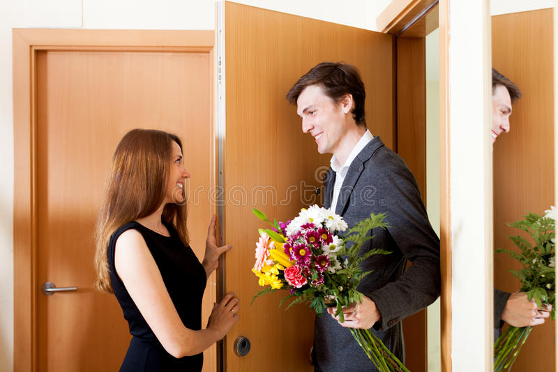 Cute couple greeting in the doorway. At home stock image