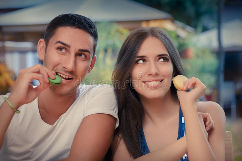 Cute Couple Having Macarons at a Restaurant royalty free stock images