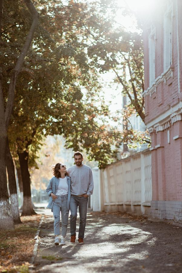 Cute couple holding hands walking in street stock images