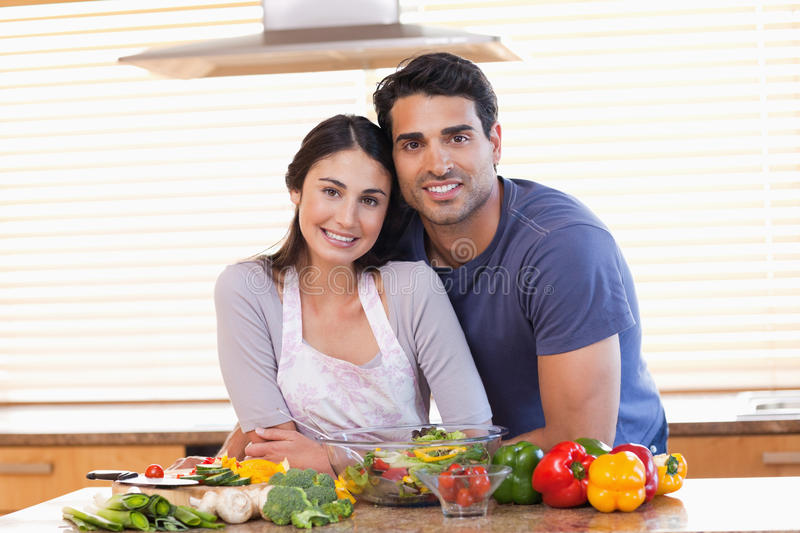 Cute couple looking at the camera. In their kitchen stock image
