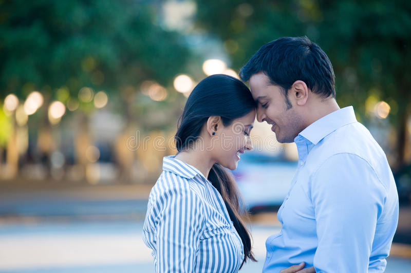 Cute couple in love. Closeup portrait, young couple in blue shirt, head to head, eyes closed in love smitten, isolated outdoors outside background. Happy moments royalty free stock photos