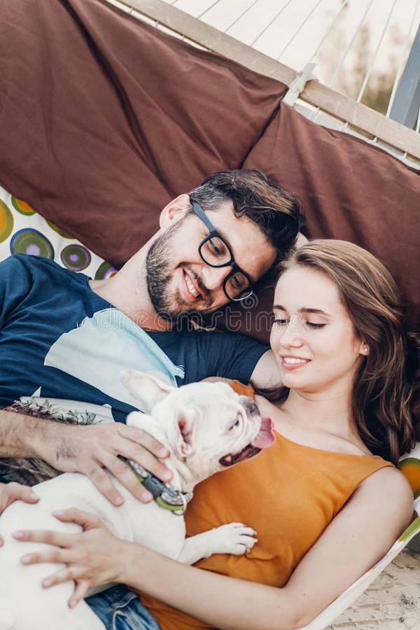 Cute couple lying in a hammock with a dog, funny white bulldog relaxing with a hipster young family on a beach, family portrait royalty free stock photo