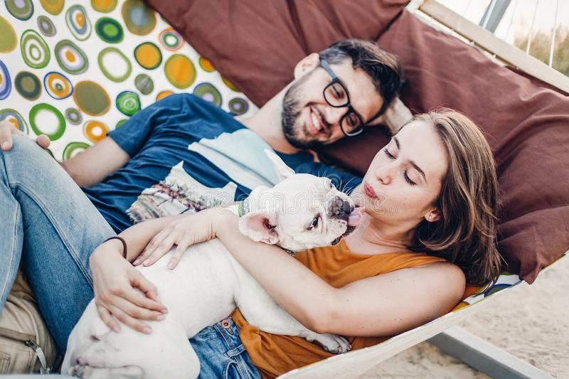 Cute couple lying in a hammock with a dog, funny white bulldog relaxing with a hipster young family on a beach, family portrait stock images