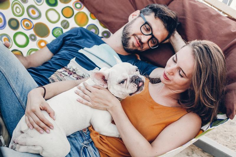 Cute couple lying in a hammock with a dog, funny white bulldog relaxing with a hipster young family on a beach, family portrait royalty free stock image