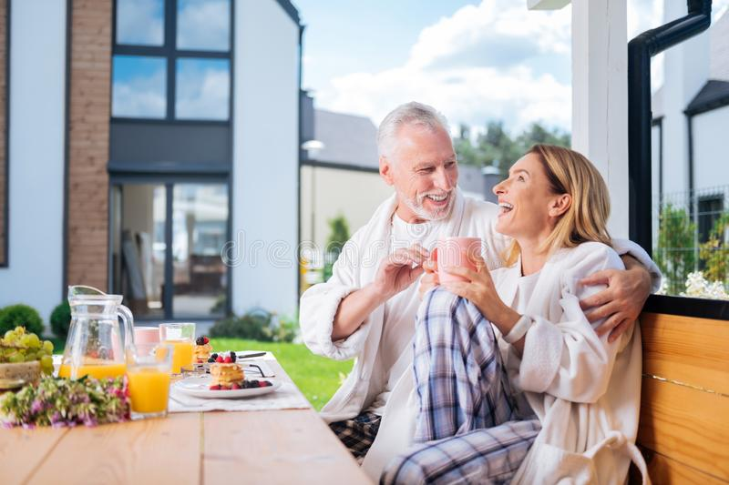 Cute couple of mature man and woman laughing while joking during breakfast stock photos