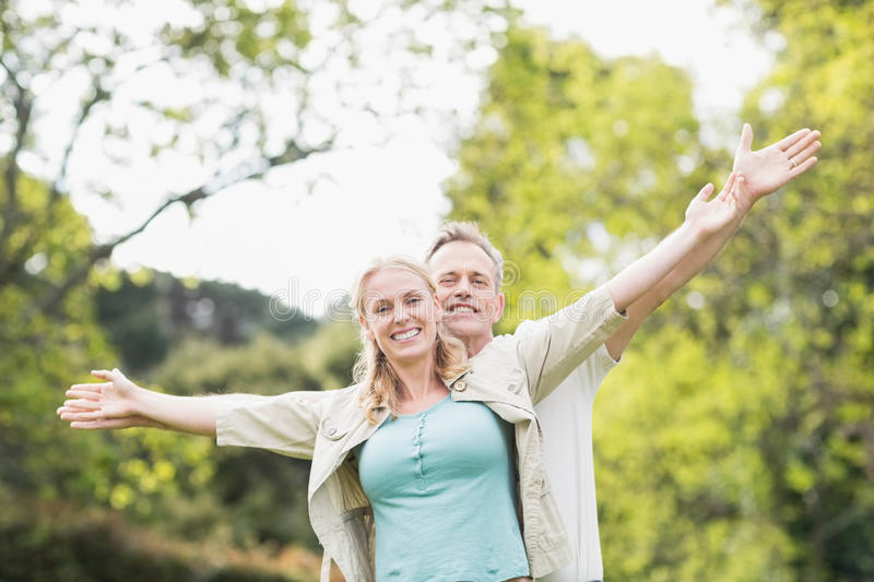 Cute couple raising arms. Outside stock photos