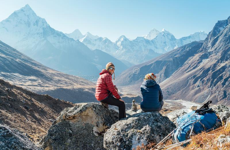 Cute Couple resting on the Everest Base Camp trekking route near Dughla 4620m. Man smiling to woman.Backpackers left Backpacks and stock photos