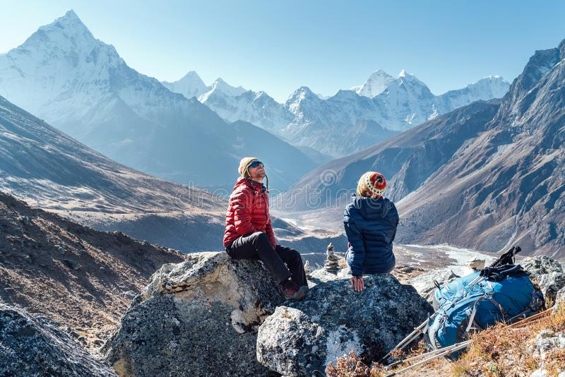 Cute Couple resting on the Everest Base Camp trekking route near Dughla 4620m. Man and woman enjoying a rest.They left Backpacks. Cute Couple resting on the royalty free stock image
