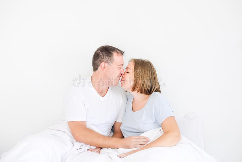 Cute couple in sleepwear on the bed. Husband holding hand on stomach of his pregnant wife. Happy and loving family morning concept stock images