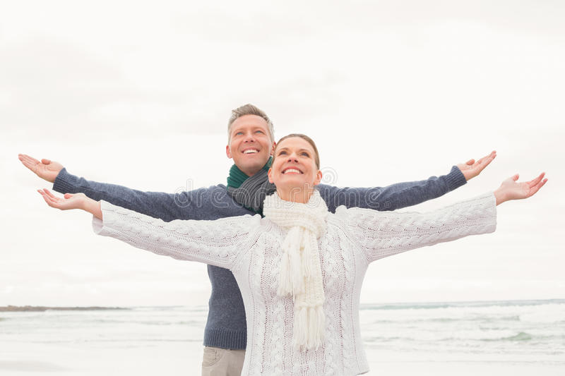 Cute couple standing with arms open wide royalty free stock photography