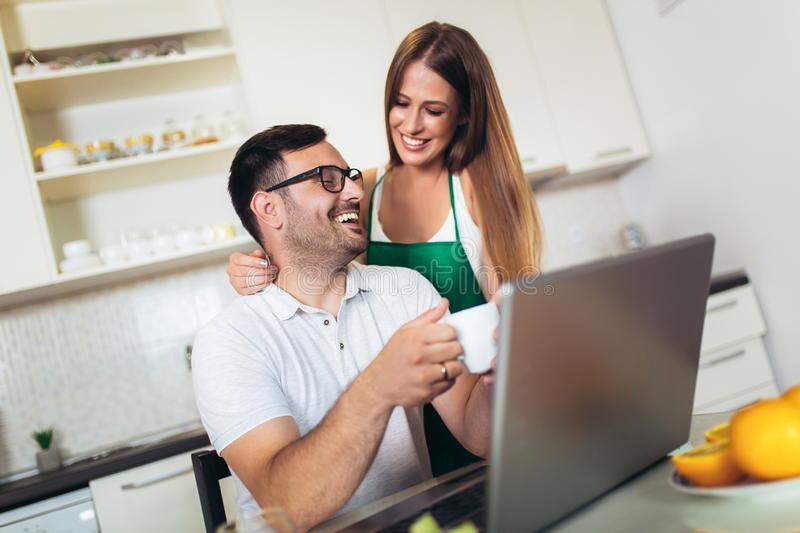 Couple using laptop together at home in the kitchen stock photography