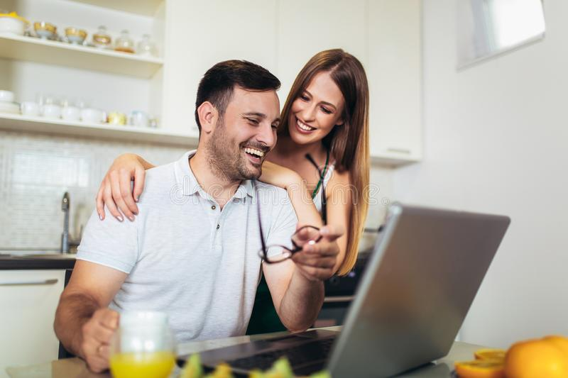 Couple using laptop together at home in the kitchen stock images