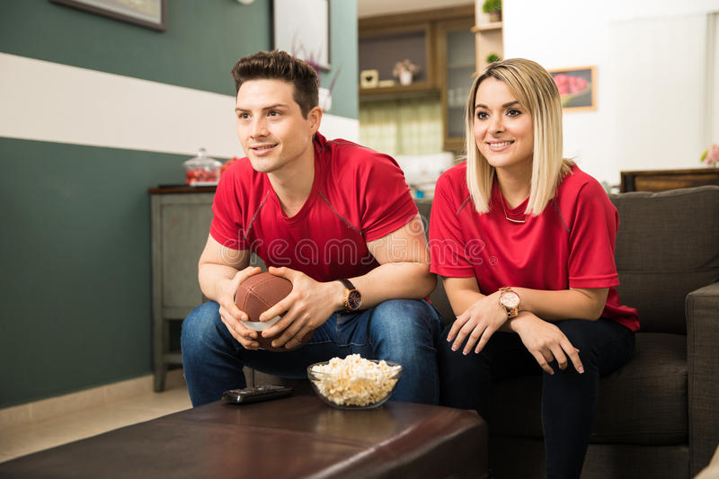 Cute couple watching a football game royalty free stock photography