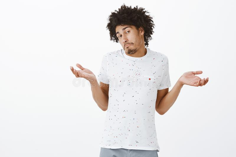 Cute coworker telling boss doubt work can be done in time. Unaware clueless handsome hispanic tanned male with moustache. And afro hairstyle, shrugging with stock photos