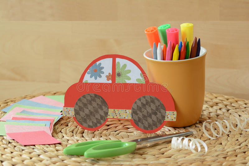 Cute crafty hand made red car for kids with colorful pastels and scissors. Cute crafty hand made red car for kids with colorful pastels, markers, papers, and stock photos