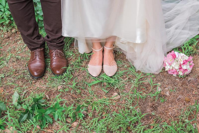 Cute cropped picture of groom`s and bride`s shoes standing together on the grass stock photography