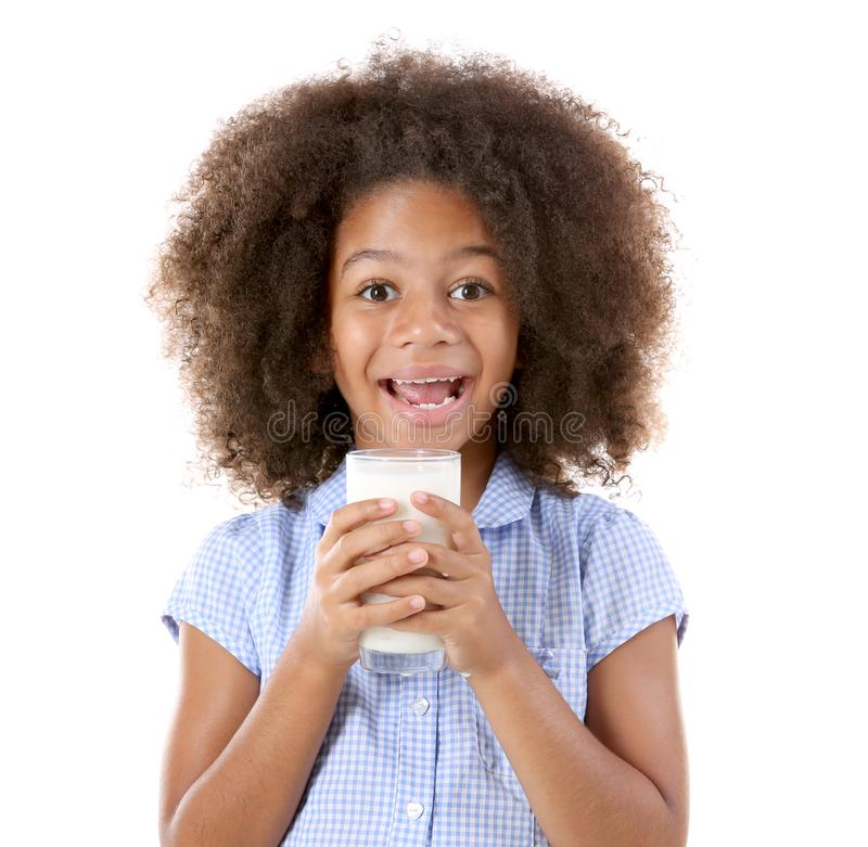 Cute curly African-American girl drinking milk. On a white background stock photography