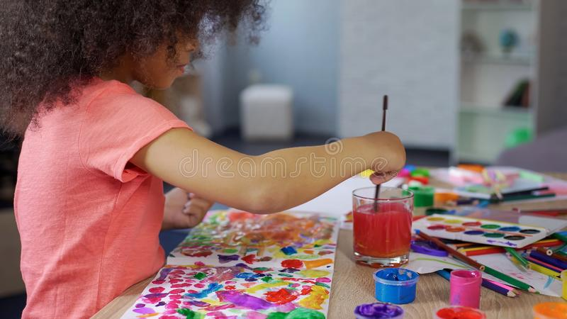 Cute curly African American girl putting paintbrush into water, leisure time royalty free stock photo