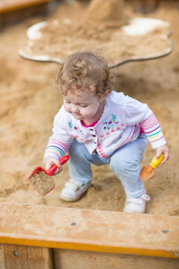Cute curly baby girl digging in sand on a playground. Cute curly little baby girl digging in sand on a playground royalty free stock photo