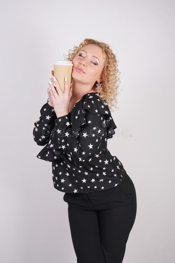 Cute curly blonde girl stands in black fashionable clothes and holds a paper Cup of coffee on a white Studio background stock photo