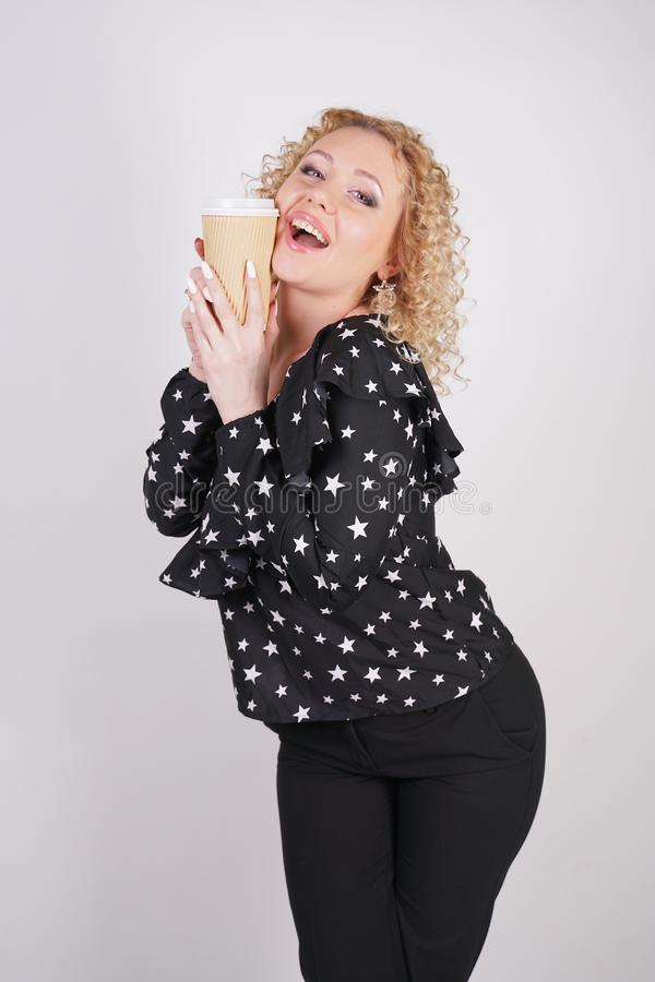 Cute curly blonde girl stands in black fashionable clothes and holds a paper Cup of coffee on a white Studio background stock photography