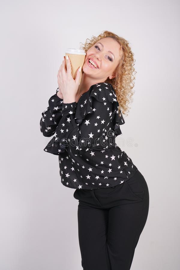Cute curly blonde girl stands in black fashionable clothes and holds a paper Cup of coffee on a white Studio background royalty free stock photo