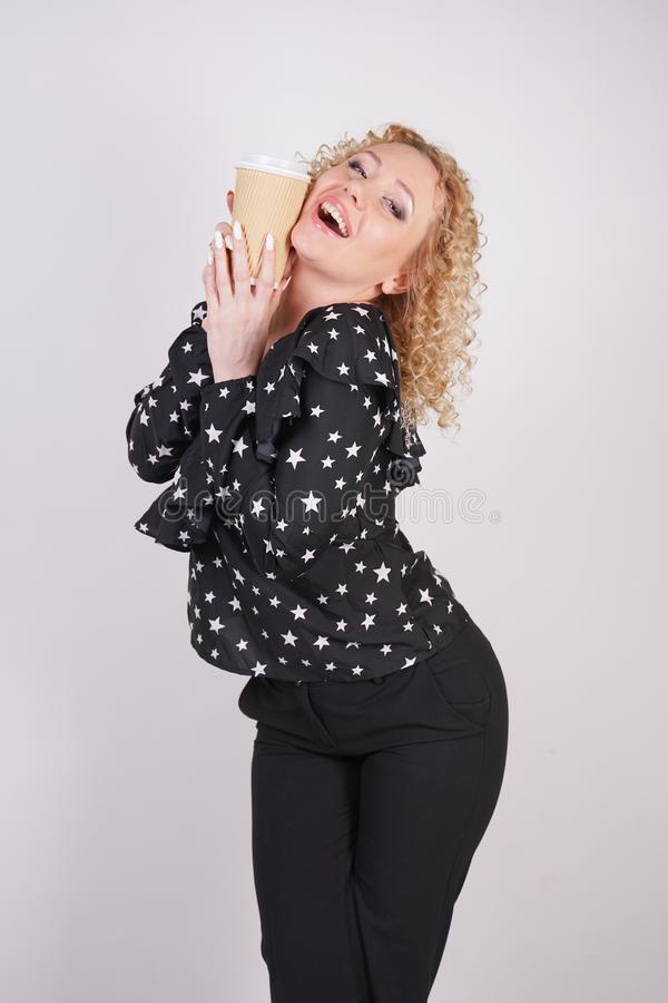 Cute curly blonde girl stands in black fashionable clothes and holds a paper Cup of coffee on a white Studio background royalty free stock image