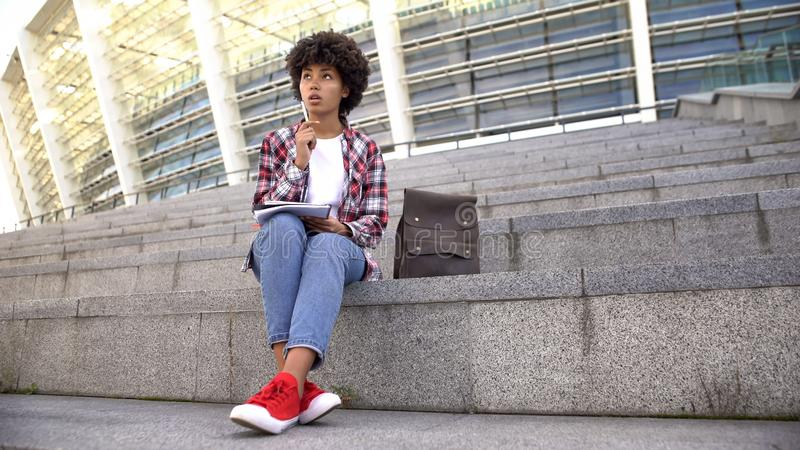 Cute curly haired female student doing homework, sitting on stairs near arena stock images