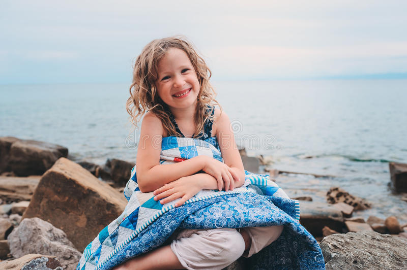 Cute curly happy child girl relaxing on stone beach, wrapped in cozy quilt blanket. Summer vacation activities, traveling in Europe on holidays royalty free stock photos