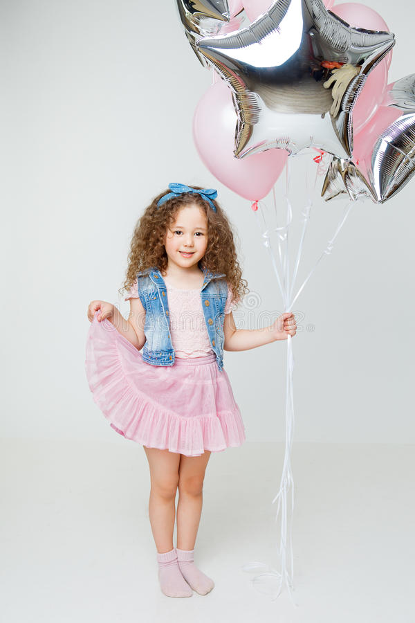 Cute curly little girl in pink skirt smiling and holding baloons. Celebration stock images
