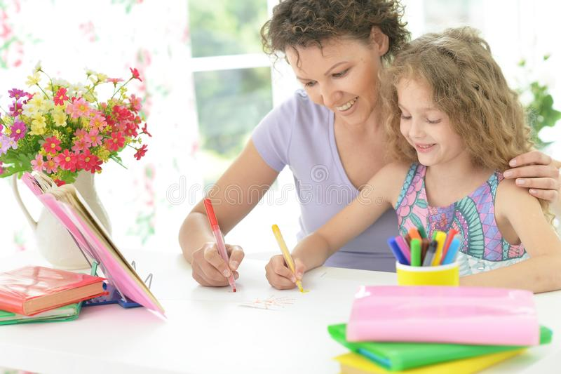 Curly schoolgirl with mother drawing at home royalty free stock image