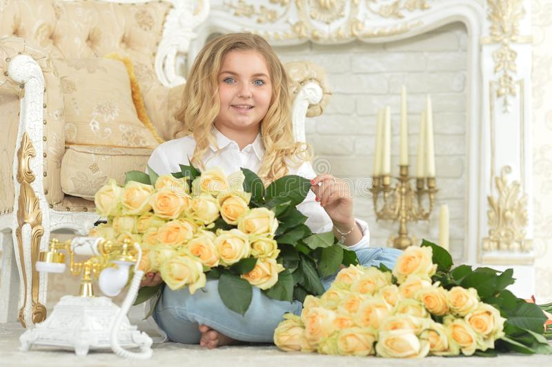 Cute curly teen girl posing with bouquet of yellow roses royalty free stock photo