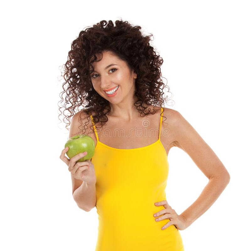 Cute curly woman with beautiful snow-white smile in yellow lingerie holding green apple. Healthy lifestyle and nutrition, dieting royalty free stock photo