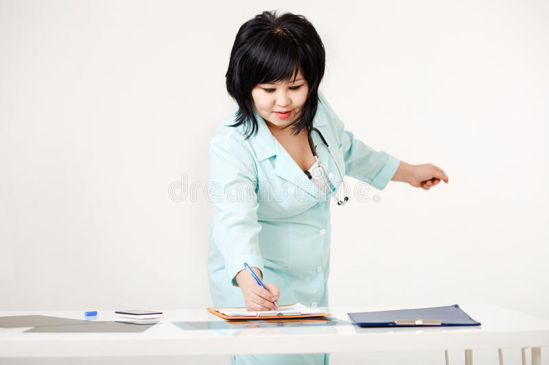 Cute curvy female doctor standing at her desk writes results of survey on paper by pen, medical lab coat with stock photos