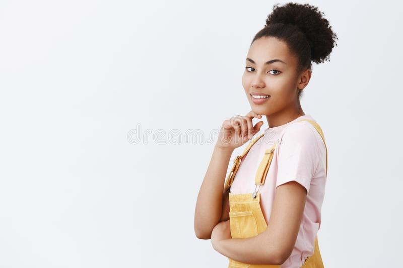Cute customer inviting girlfriend on date after part-time job. Portrait of charming sensual feminine girl in yellow stock image