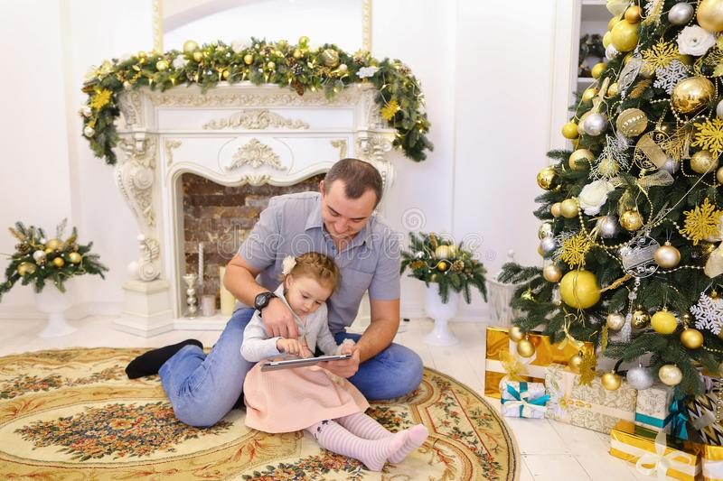 Cute Daddy Daughter and dad playing on tablet sitting on floor i royalty free stock image