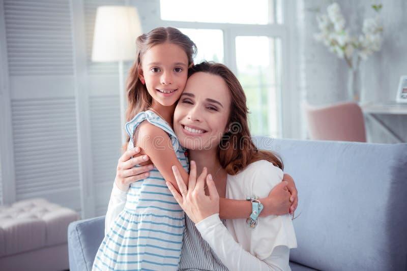 Cute dark-eyed daughter hugging her beaming caring mother stock image
